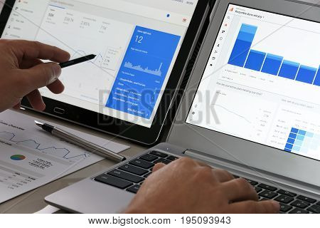 Krynica-Zdroj Poland - July 11 2017: Businessman using Google Analytics in the office on the touch screen of his tablet and laptop. Google Analytics is the most famous application for advanced web traffic analysis in the world