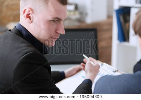Group of people deliberate on problem with clipboard pad closeup. White collar check money papers stock exchange market earnings list partnership agreement idea discussion startup concept