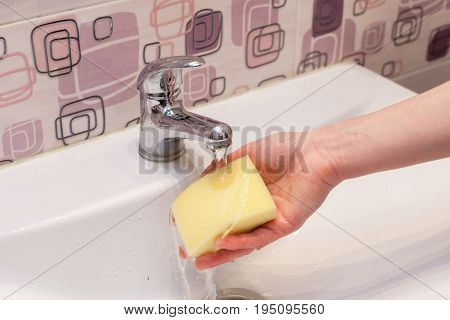 Housewife rinsing off a sponge for cleaning the bathroom under the running water from the hand basin.