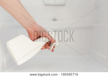 House cleaning - plastic bottles with detergents in kitchen fridge. Close-up of person hand cleaning refrigerator with spray bottle