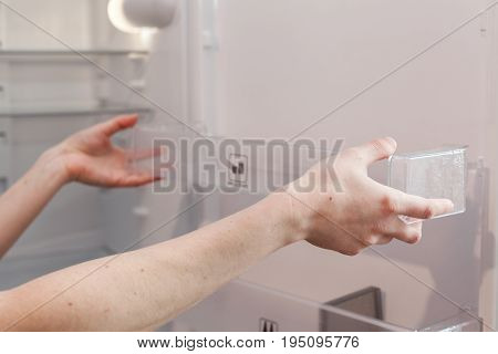 Installing new clean shelves in an empty washed refrigerator. Young woman cleaning refrigerator.