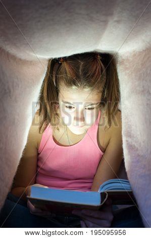 Young cheerful teenage girl hiding under blanket and enrapt reading interesting book at nighttime. Key light coming from book. Indoors vertical image.