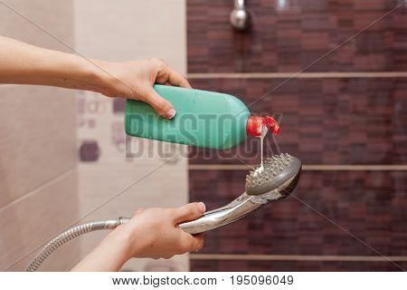 Woman hands with bottle of cleaning detergent for bathroom applies a scour to the metal shower head
