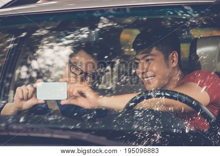 Smiling Asian friends taking selfie on smartphone while sitting in car before unforgettable road trip, view thorough windshield
