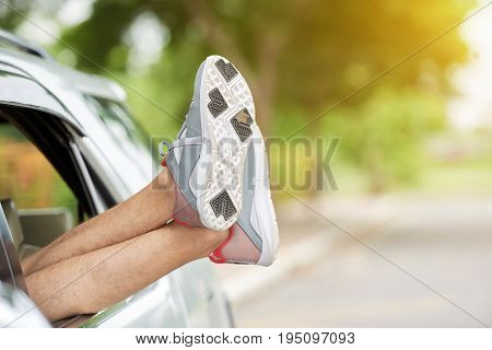 Male legs leaning out of car window, blurred background