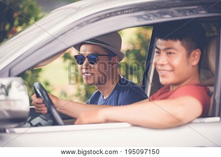 Profile view of smiling Vietnamese tourists having fun during long-awaited road trip