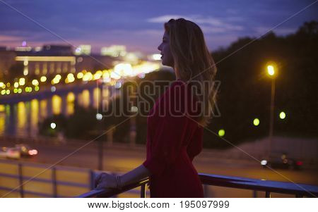 Gold time shooting. Young beautiful woman in a long red dress is standing near parapet. Sunset in Moscow. High angle view of the city and the river.
