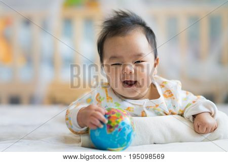 Newborn boy smile on the bed with world model baby newborn world environment saft world generation of human and kid concept.