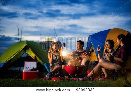 Camping of asian man and women group relaxing sing a song and cooking with ligh from car and tent