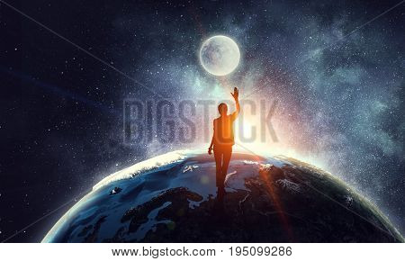 Young woman reaching moon