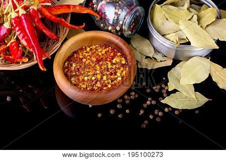 Spices and herbs, bay leaf, black peppercorn, red chili peppers and wooden bowl of chili flakes on black background with reflection