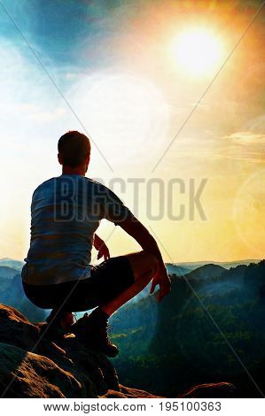 Film Grain. Young Hiker In Black Pants And Shirt  Is Sitting On Cliff's Edge And Looking To Misty Hi