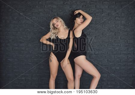 Two Attractive Girls Posing On A Black Brick Wall Background