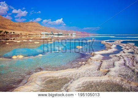 Hot summer day on the Dead Sea. The evaporated salt has developed into fantastic patterns. The concept of medical and ecological tourism