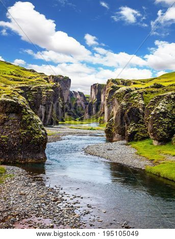 Canyon Icelandic fairy tales and legends - Fyadrarglyufur. Steep cliffs, overgrown with green moss, surrounded by river with cold water