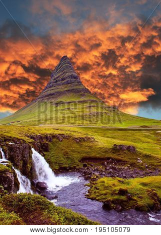 The most famous mountain in Iceland is Kirkufell. At the foot of the mountain cascading waterfalls Kirkjoufellfoss. Magic sunset. The concept of exotic and extreme tourism
