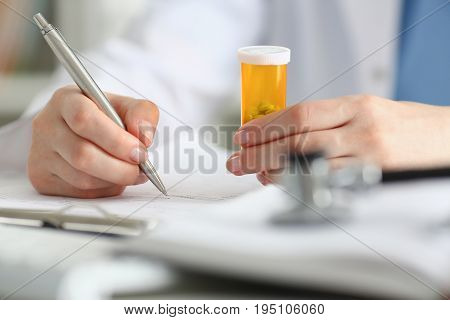 Female Doctor Hand Hold Jar Of Pills And Write Prescription