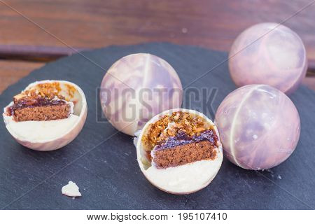 An unusual cake in chocolate balls and caramel cube from isomalt. Each bowl contains a filling of walnut mushrooms, chocolate brownies, almond praline and strawberry marmalade.