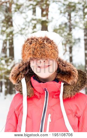 Funny young cheerful laughing girl in warm earflap having fun in winter forest. Bright vibrant outdoors vertical image.