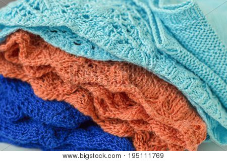 Pile of warm knitted fabric of blue and orange color. Handmade knitwear
