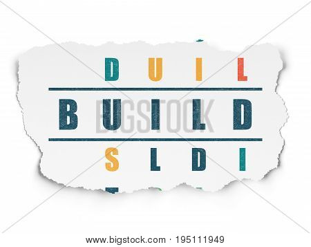 Construction concept: Painted blue word Build in solving Crossword Puzzle on Torn Paper background