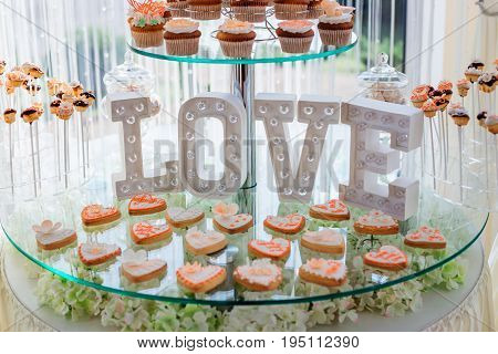 Cookies Decorated With White And Orange Glaze Stand Before White Lettering Love