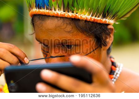 Native Brazilian man from Tupi Guarani tribe painting his face, Brazil