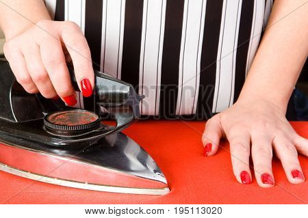 Female hands with red nails and an old electric iron. Ironing clothes.