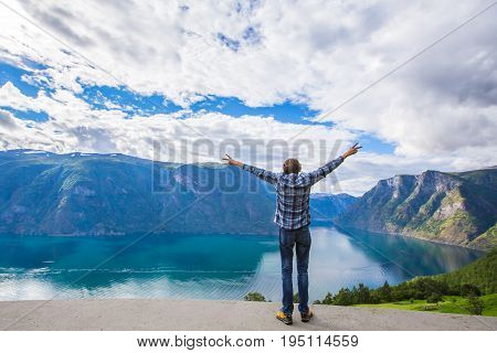 Freedom traveler man standing upper the fjord and enjoying a beautiful nature. The man straightened his arms and standing on a cliff enjoying views of the mountains. Norway nature turism and traveler.