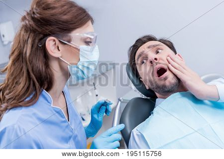 Scared Patient Looking At Dentist In Protective Mask With Dental Tools In Hands