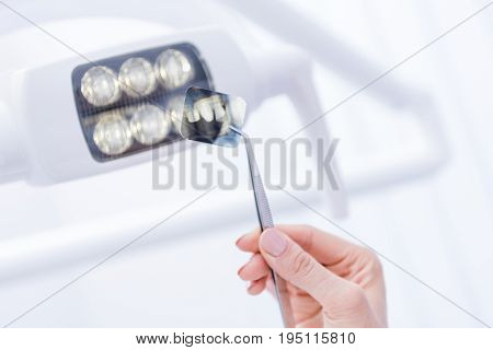 Cropped Shot Of Dentist Holding Xray Picture Of Teeth With Forceps Against Dental Lamp