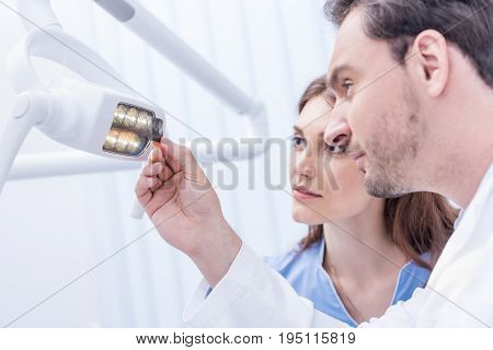 Side View Of Dentists Looking At Xray Picture Of Teeth In Hand Against Dental Lamp