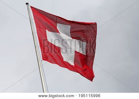 Classic view of the national flag of Switzerland waving in the wind against sky on a sunny day in summer on the First of August the national holiday of the Swiss Confederation