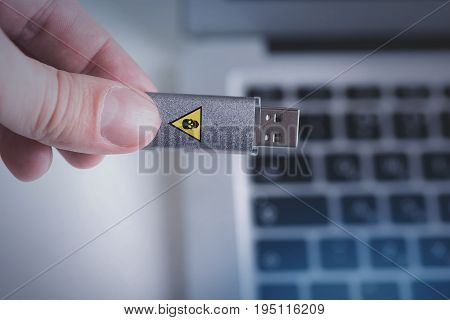 Threats of USB drives concept. Close up top view of flash memory stick with virus risk which man is holding in his hand against keyboard of laptop