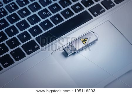 Security risks from USB flash stick concept. Close up top view of memory device infected virus is on keyboard of laptop