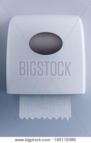 close up view of paper towel dispenser made of white plastic on wall