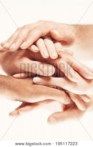 Closeup of multiethnic men and women piling hands on top of each other against white background