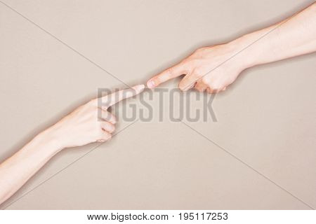 Two hands with fingers tip to tip symbolizing contact or connection against gray background