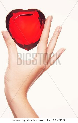 Closeup of a hand holding up heart shaped jewel between finger and thumb against white background