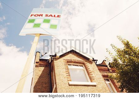 Low angle view of sale sign in front of new house against cloudy sky
