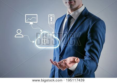 Protecting personal data. Pleasant businessman is demonstrating model of cloud network connection to computer, smartphone and users. Internet risk and data security concept