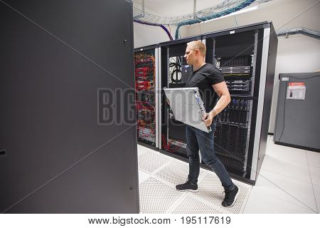 Full length of male IT engineer carrying blade server while walking in datacenter