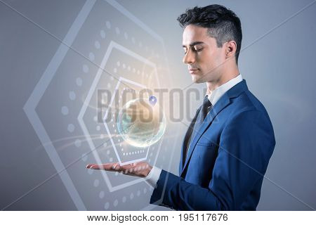 My location. Thoughtful young pleasant businessman is looking at 3D model of planet with geolocation information while standing against blue wall