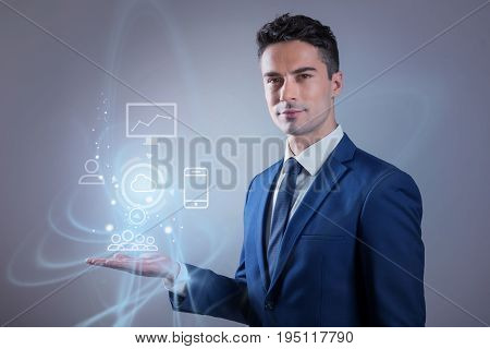 Model interconnections. Portrait of young businessman is demonstrating of modelling complex connected systems submitted by icons of modern devices which are connecting to cloud