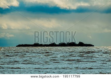 Dark scene with an isolated distant island in the sea and thin light horizon