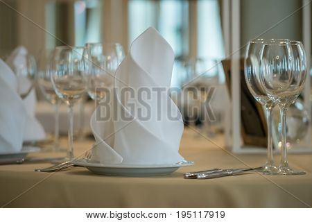 Empty glasses set with napkins in a restaurant