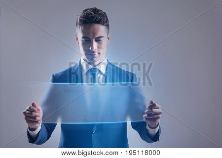Global business concept. Successful young man is working with transparent digital touchscreen. He is standing with gadget and looking at screen with slight smile