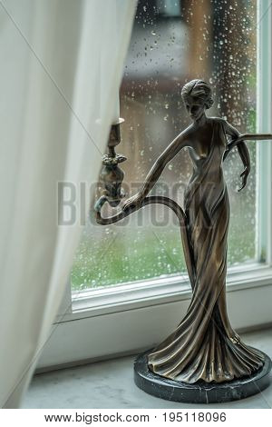Vintage candlestick with candles on a background of a rainy window. Soft focus, selective focus