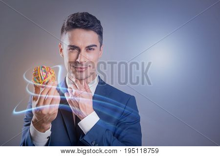 Enthusiasm concept. Portrait of young positive businessman is standing with small colorful ball. He is touching his chin and looking at camera with joy. Copy space in the right side