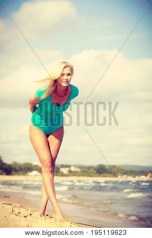 Sumer time leisure concept. Beautiful woman standing with costume. Lady enjoying good sunny weather outside.
